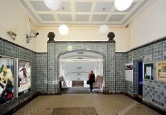 Restaurierte Innenraum / Eingangsraum der U-Bahnstation Schmalenbeck; runde Lampen, farbig glasierte Kacheln an den Wänden.