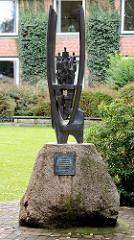 Kunst im Öffentlichen Raum - Metallskulptur auf einem Findling - Inschrift: SYNERGIA - Das Zusammenwirken schöpferischer Kräfte in Wissenschaft und Technik. In ihr sind wir geborgen aber auch gefangen. Siegfried J. Assmann.