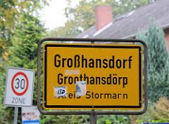 Ortsschild Großhansdorf - Plattdeutsch Groothansdörp, Kreis Stormarn; gelber Grund mit schwarzer Schrift.