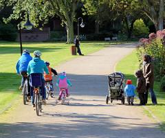 Kurpark Mölln - 2007 unter Denkmalschutz gestellt - 1968 eröffnet, Entwurf Hamburger Gartenarchitekt Gustav Lüttge. Familie mit Fahrrad - Kinderfahrrad; Spaziergänger mit Kindern und Kinderkarre.