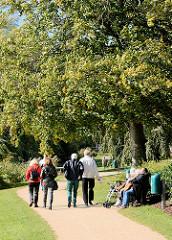 Spaziergängerinnen am Wanderweg des Schulsees. Sonnenhungrige auf einer Holzbank unter einem Baum in der Sonne.