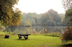 Herbstlich gefärbte Bäume am Mühlenteich in Grosshansdorf; Herbstfarben. Sitzbank / Sitzgruppe aus Holz, Picknickplatz auf einer Wiese am Wasser.