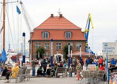 Hafenpromenade in der Hansestadt Wismar - Hafenbesucher sitzen auf Bänken - im Hintergrund  das Alte Baumhaus und ein Hafenkran.