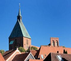 Kirchturm der Möllner St. Nicolai-Kirche über den Dächern der Altstadt; re. der Giebel des Möllner Rathauses.