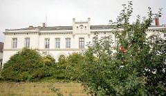 Altes Bahnhofsgebäude Wismar - im Vordergrund stillgelegte Gleisstrecken. Ein Apfelbaum trägt Früchte.