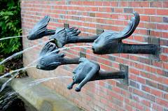 Brunnen Kurpark Mölln; Wasserspeier - Wasser speiende Bronzeköpfe - Kunststil der 1960er Jahre.