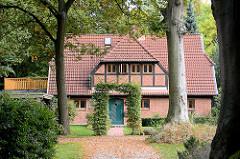 Architektur in der Gemeinde Großhansdorf - neuerbautes Fachwerkhaus mit Ziegelfüllung; hohe Bäume