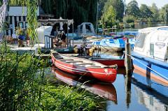 Bootsvermietung  am Stadtsee von Mölln - ein rotes Kanu liegt am Schilf des Sees - im Hintergrund Tretboote.