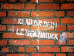 Graffiti auf rotem Ziegel - Silo im Hafen der Hansestadt Wismar: KLAU DIR DEIN LEBEN ZURÜCK.