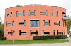 Moderne Architektur - mehrstöckiges rundes Wohnhaus - rote Fassade; Architekturbilder aus der Hansestadt Wismar.