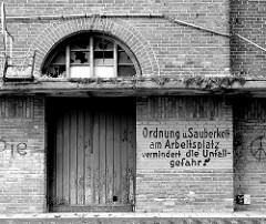 Verlassene Industriearchitektur im Hafengebiet Wismars - Schild ORDNUNG UND SAUBERKEIT AM ARBEITSPLATZ VERMINDERT DIE UNFALLGEFAHR; zerbrochene Scheiben.