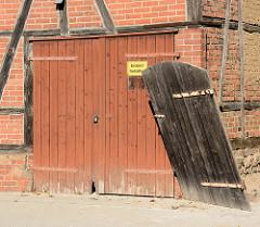 Garagentor an einem Fachwerkhaus in Mölln; in den Angeln hängende schiefe Holztür.