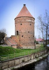 Befestigungsturm - alte Stadtmauer in Dobre Miasto / Guttstadt, Polen - Storchenturm mit Storchennest auf der Spitze; im Vordergrund der Fluss Lyna / Alle.
