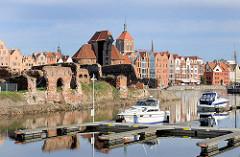 Sportboothafen, Marina in Danzig - Maurerreste von Backsteinspeichern auf der Danziger Speicherinsel - im Hintergrund das historische Krantor und Gebäude der Altstadt Danzigs / Gdansk.