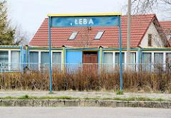 Bahnhof, Bahnsteig - Ortsschild Łeba; im Hintergrund Wohncontainer.