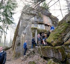 Touristen auf dem Gelände der Wolfsschanze  /  Wilczy Szaniec - einige klettern auf den Betontrümmern oder besichtigen einen zerstörten Bunker.