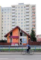 Moderne Architektur - Plattenbauten mit farbiger Fassade und bunt abgesetzten Balkons - Fotos aus Malbork / Marienburg, Einzelhaus mit orangenfarbiger Fassade, Fahrradfahrer.