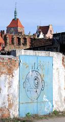 Ziegelmauer, Metalltor mit Graffiti auf der Danziger Speicherinsel - im Hintergrund die Altstadt von Danzig.