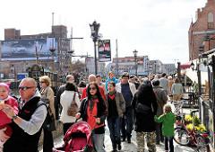 Touristen auf der Hafenpromenade von Danzig.
