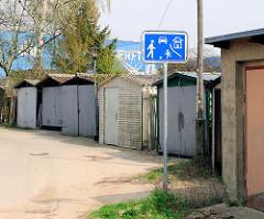 Schild Spielstrasse in Wolgast - Garagen und Schuppen; im Hintergrund ein Werftgebäude der Peene Werft.