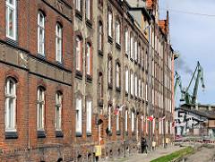 Historische Architektur - Arbeiterwohnungen, Etagenwohnungen - im Hintergrund Kräne der Danziger Werft - stocznia Gdańsk.