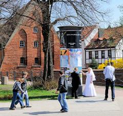 Kleine Mühle in Danzig - errichtet im 14. Jahrhundert über dem Radaunekanal; gotisches Backsteingebäude. Fotosession auf der Strasse - Hochzeitsfotografie / Hochzeitsfotograf mit Brautpaar zwischen Passanten.