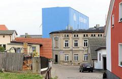 Wohngebäude in Wolgast - im Hintergrund ein Werftgebäude der Peene Werft.