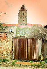 Wellblechtor an einer Mauer mit abbröckelndem Putz - im Hintergrund der Kirchturm der gotischen Marienkirche in Anklam, Mecklenburg-Vorpommern.