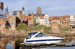 Sportboot in der Marina der Stadt Danzig - dahinter Mauerreste, Backsteinmauern der zerstörten Speichergebäude auf der Speicherinsel und historische Architektur, Gebäude der Danziger Altstadt an der Mottlau.