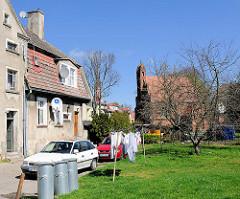 Wohnhaus - Wäsche auf der Leine zum Trocken auf dem Rasen hinter dem Haus - im Hintergrund eine Kapelle - Backsteingotik; historische Architektur in Trzebiatow / Treptow an der Rega.