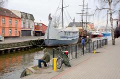 Angler im Hafen von Łeba, Polen - am Kai Ausflugsschiffe für Touristen, nachgebaute Koggen.