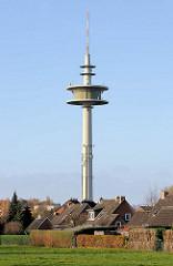Fernmeldeturm Bad Segeberg - dient Richt- und Mobilfunkzwecken und hat eine Höhe von 133 m. Im Vordergrund eine Wiese und Einzelhäuser mit Spitzdach.