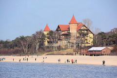 Ehem. Kurhaus am Ostseestrand von Łeba / Leba, erbaut Ende des 19. Jahrhunderts - jetzt Hotel Neptun. Touristen gehen am Strand spazieren.