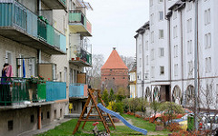 Mehrstöckige Wohnhäuser mit farbigen Balkons - Wiese mit Kinderspielplatz; im Hintergrund der sogen. Storchenturm, Teil der Befestigungsanlage von Dobre Miasto / Guttstadt, Polen.