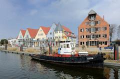 Alter Hafen von Wolgast - historisches Speichergebäude; Ziegelspeicher, erbaut 1835  - Neubauten an der Hafenpromenade; der alte Hafenschlepper Steppke liegt am Kai.