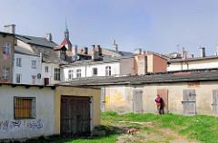 Schuppen mit Holztüren im Hinterhof, Hund auf der Wiese - Hausdächer von Darłowo / Rügenwalde, Polen. Im Hintergrund die Spitze vom Kirchturm der gotischen Marienkirche.