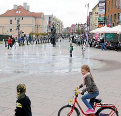 Geschäftsstrasse in   Malbork / Marienburg, Polen; Springbrunnen auf einem Platz - Cafe auf der Strasse, spielende Kinder.