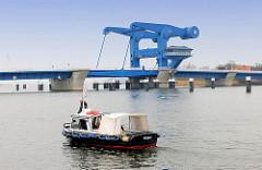Peenebrücke in Wolgast - Klappbrücke über den Peenestrom, erbaut 1996 - Gesamtlänge 247 m; Sportboot auf der Peene.