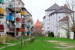 Mehrstöckige Wohnhäuser mit farbigen Balkons - Wiese; im Hintergrund der sogen. Storchenturm, Teil der Befestigungsanlage von Dobre Miasto / Guttstadt, Polen.