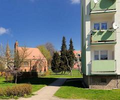 Balkons, mintgrüne Fassade; Neubau - Mietswohnungen - im Hintergrund eine Kapelle - Backsteingotik; historische Architektur in Trzebiatow / Treptow an der Rega.