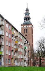 Kirchturm der St. Peter und Paul in Lidzbark Warmiński / Heilsberg. Mehrstöckige Wohnhaus mit Balkons.