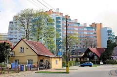 Einzelhaus mit Spitzdach und gelber Fassade - Hochhausanlage mit farbigen Balkons im Hintergrund - Architektur in Międzyzdroje / Misdroy (Polen); al