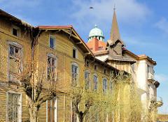 Leerstehendes altes Gebäude mit Holzfassade - verfallene histoirsche Architektur in 4430 4433 Alte Wohnhäuser, historischer Baustil - moderne Wohnblocks mit farbigen Balkonbrüstungen in Międzyzdroje / Misdroy (Polen).