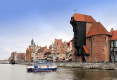 Hafenpanorama der Hafenstadt / Hansestadt Danzig - historische Gebäude auf der Wasserseite / am Ufer der Mottlau - Krantor; eine Personenfähre kreuzt den Fluss.