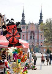 Barockarchitektur - Marienwallfahrtsort Święta Lipka, Heiligelinde - Polen. Andenkenverkauf - Souvenirstand an der Strasse; im Hintergrund die barocke Fassade und Kupfertürme der Kirche.