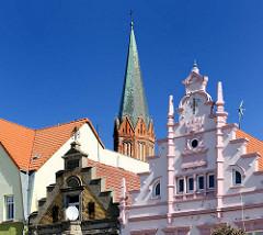 Restaurierte Bürgerhäuser am Marktplatz von Trzebiatow / Treptow an der Rega - Kirchturm der Marienkirche.