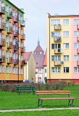 Neubauten, Plattenbauten mit bunter Fassade und Balkons - leere Sitzbänke auf dem Rasen - im Hintergrund die gotische Backsteinkirche St. Marien. Historische und moderne Architektur, alt + neu.