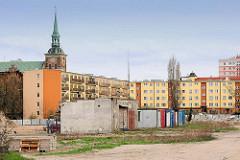 Etagenhäuser - Neubauten; Kirchturm - Architektur in der polnischen Stadt Danzig / Gdansk.