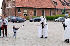 Hof der Ordensburg in Malbork / Marienburg, Polen. Als Ordensritter verkleidete Männer spielen mit einem Kind Schwertkampf.