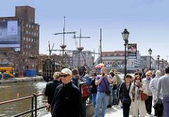 Touristen auf der Hafenpromenade von Danzig - im Hintergrund Gebäude auf der Speicherinsel.